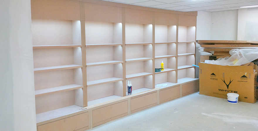 Cycle shoe and helmet cupboard lit and ready for painting at Rutland Cycling's new Cambridge store.