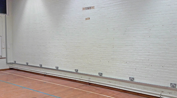Trunking and sockets work in a school gym.